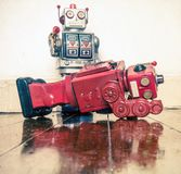 Shot down robots. Shot down concept with retro tobot toys on a wooden floor with reflection Stock Photos