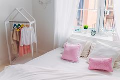 Shot of empty bedroom with no people, pink pillows, big window, alarm clock and handmade picture. Cozy interior royalty free stock photo