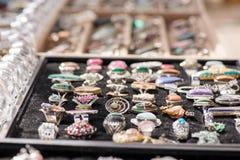 Shot of expensive gemstone jewelry. Rings made of amethyst, sapphire, rose quartz, moonstone, blue topaz, tanzanite, chrysoprase,. Diamond, charoite stones Royalty Free Stock Images