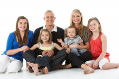 Shot Of Family Group Sitting In Studio. On White Background stock photo
