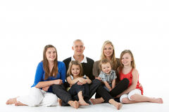 Shot Of Family Group Sitting In Studio. On White Background stock photos