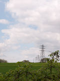 A shot of far away field green and with several lined up electri Royalty Free Stock Photos
