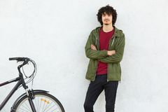 Shot of fashionable guy has curly hair, dressed in anorak, keeps hands crossed, poses near his sports bicycle, isolated over white. Background, waits for friend royalty free stock photos