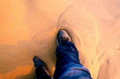 Man wearing running shoes in the sand. Shot of feet of man wearing sports shoes and blue jeans sitting on the sand of desert Royalty Free Stock Photos
