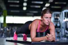 Shot of a fit young woman doing stretching workout on the gym floor. Royalty Free Stock Photo