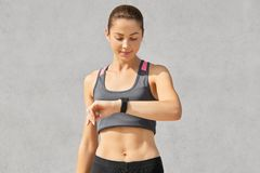 Shot of fitness lady or jogger looks attentively at smart watch, checks pulse and counts calories, has healthy lifestyle, goes in. For sport regularly, dressed stock images