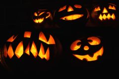 Various creatively carved pumpkins in the dark for Halloween royalty free stock image