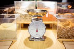 Food weighing machine and different types of condiments in bulk in an organic store. Shot of food weighing machine and different types of condiments in bulk in stock images