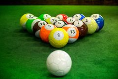 Foot pool balls standing on green table. Shot of foot pool balls standing on green table. Foot Pool is the hybrid combination of pool and soccer. Big billiard Royalty Free Stock Photo