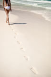 Shot of footprints with woman walks on the tropical beach Stock Photo