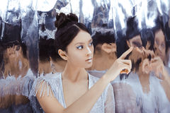 Shot of a futuristic young asian woman. Portrait of futuristic young woman touching reflection in mirror. Reflection of our mind and soul concept. Beautiful Stock Photos