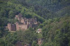 Ruined german castle in forrest mountain landscape. Shot of a German ruined castle during day lying between hills in a forrest Stock Image