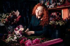 Ginger woman standing at table and making floral composition at flower shop. Shot of ginger woman standing at table and making floral composition at flower shop stock photo