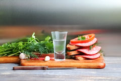 Shot glass of alcohol sweated and sandwiches with greens, cold meats and tomatoes Royalty Free Stock Photos