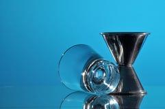 Shot glass & bartenders jigger on countertop. royalty free stock photo