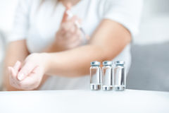 Shot of glass bottles with insulin against woman doing prick Royalty Free Stock Image