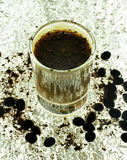 Shot Glass with Coffee Cocktail. Cocoa powder and cocoa powder on a silver shiny background Royalty Free Stock Photos