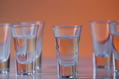 Shot glass filled with vodka on a orange background. Shot glass filled with vodka  on a orange background Stock Photo
