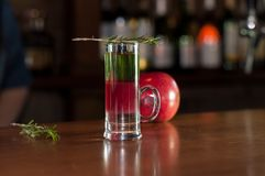 Shot glass with multicolored alcohol drink and rosemary on near red apple. Selective focus of shot glass with multicolored alcohol drink and rosemary on near red royalty free stock photo