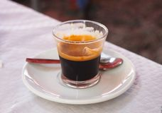 Glass of Nespresso on saucer Stock Images