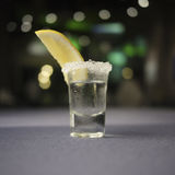 Shot glass of tequila. Side view of shot glass full of tequila with sugary rim and slice of lemon Royalty Free Stock Image