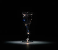 The shot glass of vodka stands in the dark on a light spot on a black background Royalty Free Stock Images