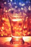 Shot glass of vodka. On shiny festive background Stock Images