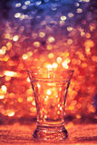 Shot glass of vodka. On shiny festive background Royalty Free Stock Images