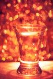 Shot glass of vodka. On shiny festive background Royalty Free Stock Photography