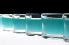 Shot Glasses. Row of shot glasses filled with blue alcohol on a white tabletop and black background Royalty Free Stock Image