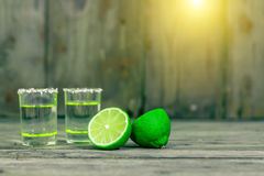 Shot glasses with golden mexican tequila with lime slices and salt on old wooden table. Selective focus. Traditional Mexican drink Stock Photos