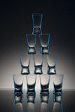 Shot Glasses on Table. A pyramid of shot glasses with reflection on a table Stock Photo