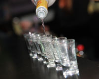 Shot glasses of vodka on the bar counter stock image