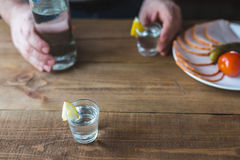 Shot glasses of vodka on a wooden table Royalty Free Stock Image