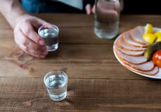 Shot glasses of vodka on a wooden table Royalty Free Stock Photography