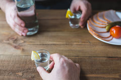 Shot glasses of vodka on a wooden table Stock Image