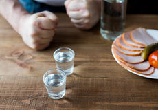 Shot glasses of vodka on a wooden table Stock Photos