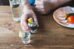 Shot glasses of vodka on a wooden table Royalty Free Stock Photos