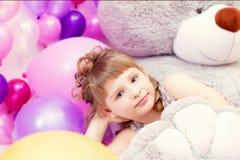 Shot of gray-eyed little girl lying on teddy bear Royalty Free Stock Image