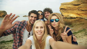 Shot of a group of friends taking a selfie on the beach. Three girls and two boys taking selfies stock footage