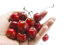 Shot of handful of red cherries on white. A handful of red cherries on white background Royalty Free Stock Images