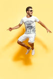 Handsome guy jumping looking at camera. Shot of handsome bearded guy dressed in white t-shirt and shorts jumping looking at camera smiling Stock Image