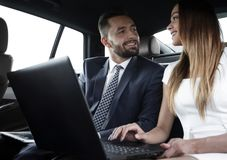 Business People Meeting Working Car Inside. Shot of a handsome confident businessman and partners traveling while working on a laptop sitting in a luxury car in Royalty Free Stock Photos