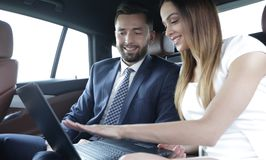 Business People Meeting Working Car Inside. Shot of a handsome confident businessman and partners traveling while working on a laptop sitting in a luxury car in Stock Photo