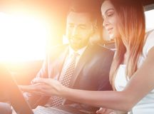 Business People Meeting Working Car Inside. Shot of a handsome confident businessman and partners traveling while working on a laptop sitting in a luxury car in Royalty Free Stock Photo