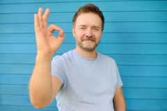 Shot of handsome mature man looking at camera and showing OK gesture. Male portrait with blue wooden wall on background. ?oncept of success stock image