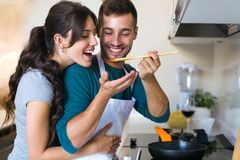 Handsome young man giving his wife to try the food he is preparing in the kitchen at home royalty free stock photo
