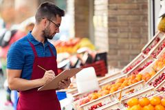 Handsome young salesman doing inventory in health grocery shop. Shot of handsome young salesman doing inventory in health grocery shop stock images