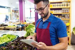 Handsome young salesman using digital tablet in health grocery shop. Shot of handsome young salesman using digital tablet in health grocery shop royalty free stock photos