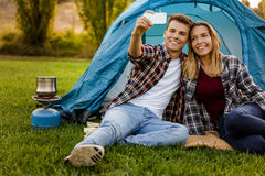 Camping time. Shot of a happy couple camping on the nature and making a selfie Stock Images